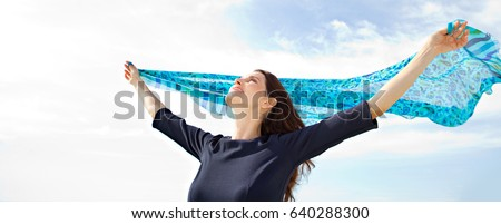 Panoramic portrait of beautiful mature woman holding raising silk fabric up against blue sky, floating in the breeze with sunshine, smiling outdoors. Positive joyful female enjoying healthy lifestyle.