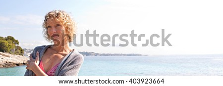 Panoramic portrait of beautiful tourist senior woman relaxing contemplating the transparent blue sea on holiday, smiling on vacation, coastal outdoors. Healthy relaxing lifestyle, nature exterior. - stock photo