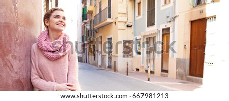Panoramic portrait of beautiful young tourist woman contemplating picturesque destination street on holiday, joyfully smiling outdoors. Recreation lifestyle, consumer on vacation city break, exterior.