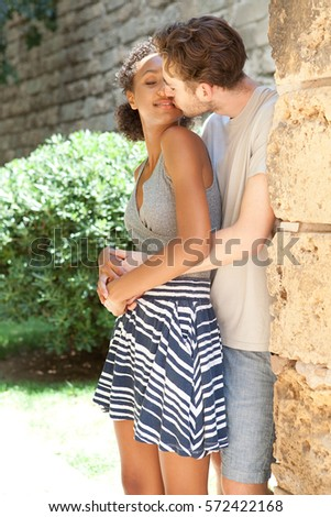 Panoramic portrait of passionate ethnically diverse tourist couple hugging kissing visiting monument park, romantic holiday in Spain, recreation outdoors. Travel lifestyle, closeness love, exterior.