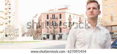Panoramic portrait of successful middle age business man in financial city district with classic office buildings, sunny avenue, looking away, outdoors. Serene confident professional male in exterior.