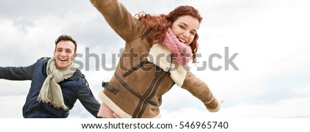 Panoramic portrait of young tourist couple running on  winter holiday, smiling joyful travel lifestyle, carefree active. Boyfriend and girlfriend recreation, fun together against sky, outdoors.