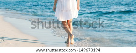 Panoramic rear lower body section view of a woman walking along a white sand beach shore at sunset, taking steps and relaxing with an intense blue sea during a summer vacation. - stock photo