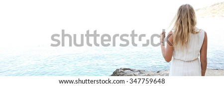 Panoramic rear view of a beautiful young woman standing on a rocky beach contemplating the blue sea on a summer holiday, relaxing outdoors. Travel and relaxing lifestyle. Serene adolescent space. - stock photo