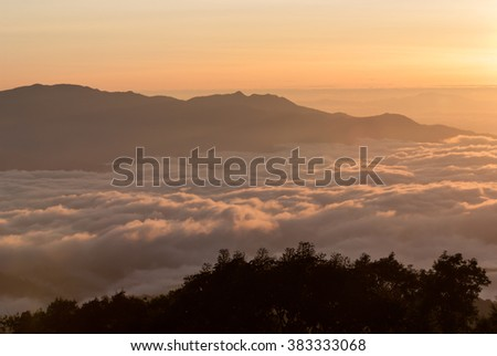 Panoramic scenery of the mist shrouded mountains at sunrise