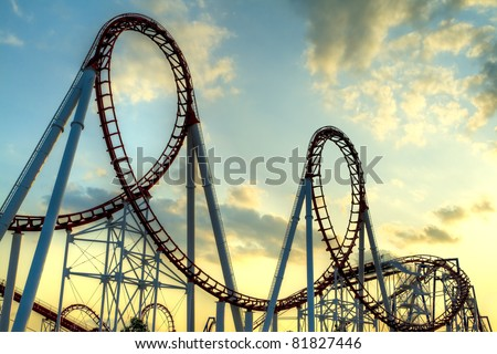 Panoramic shot of a roller coaster's loop at sunset. - stock photo