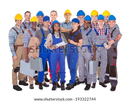 Panoramic shot of confident manual workers standing against white background - stock photo