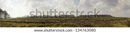 Panoramic shot of dutch farmland with cloudy sky. - stock photo