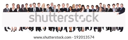 Panoramic shot of multiethnic businesspeople holding blank billboard against white background