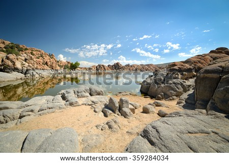 Panoramic shot of picturesque, tranquil Watson Lake, Arizona, USA on a sunny morning with sparse clouds in the bright blue sky reflecting in the calm waters  - stock photo