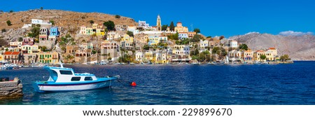 Panoramic shot of the Harbour at Symi Greece with a traditional fishing boat in the foreground. Greece Europe. - stock photo