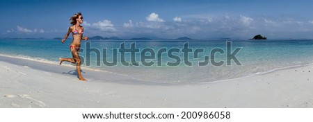 Panoramic shot of the young lady running on the sandy beach - stock photo