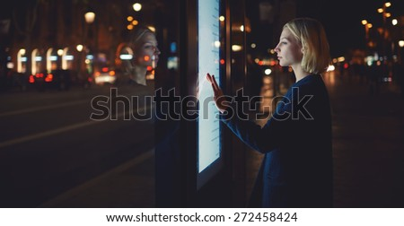 Panoramic shot, smart city technology concept,woman using modern urban application of bus stop in Barcelona for find out schedule of transport,female touching big digital screen which reflecting light - stock photo