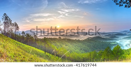 Panoramic sun rises above pine forests, clouds will gradually fade out gradually to vast green pine forests on high hills greet new day in Da lat, Vietnam - stock photo