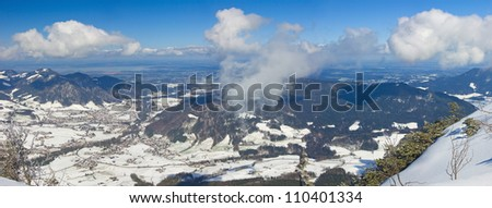 panoramic top view of Bavarian Alps with changing from white snow to green grass