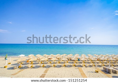 Panoramic top view of straw umbrella on an empty beach with a perfect clear blue water and sky horizon at distance. - stock photo