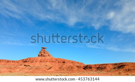 Panoramic view a red rock formation with curiously sombrero-shaped, blue sky and cloud in Utah. Mexican Hat is a census-designated place on the San Juan River in south-central San Juan County, Utah,US