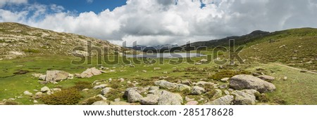 Panoramic view across Lac De Nino in Corsica with a stream meandering across a green plain in foreground and  dark clouds and snow capped mountains in the background