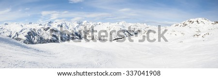 Panoramic view down a snowy mountain range valley in winter - stock photo