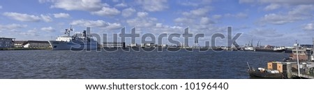 Panoramic view from Amsterdam harbor with cruiseboat in the Netherlands