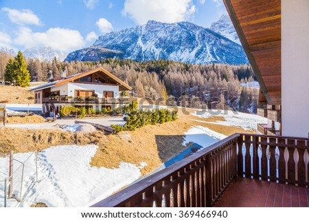 Panoramic view from balcony of traditional mountain chalet in the Alps of idyllic winter mountain scenery with on a sunny day with blue sky - stock photo