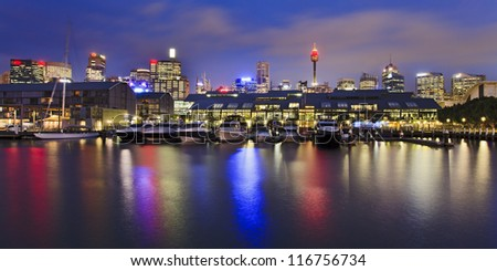 Panoramic view from Pyrmont to Sydney Australia Darling Harbour with boats at marina sunset light reflection in water