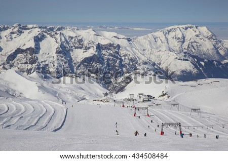Panoramic view from the glacier in Les Deux Alpes, France in the Alps in Europe, showing a nursery ski slope, chairlift, snow covered mountains with clouds below them and blue sky.  - stock photo