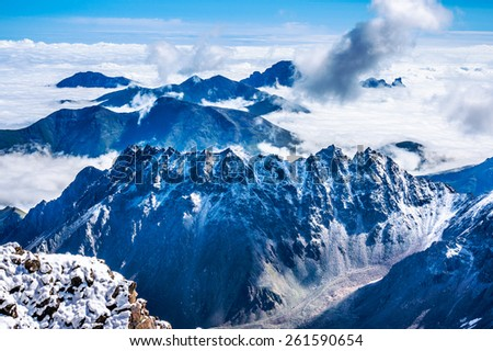 Panoramic view from the height of bird's flight over the ridges and clouds. Picture was taken during trekking hike in the magnificent Caucasus mountains, Bezengi region, Kabardino-Balkaria, Russia - stock photo