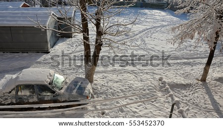 Panoramic view from window on sunny winter backyard with snow-covered car, trees and garages