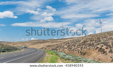 Panoramic view Interstate Highway I90 and row of wind turbines of windfarm in Ellensburg, Washington, US. Windmills again blue cloud sky. Clean energy concept. Transportation, electricity background.