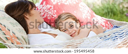 Panoramic view of a beautiful young mother and daughter laying and relaxing together on a hammock during a sunny day on holiday home garden. Family relaxing outdoors, healthy and wellness lifestyle. - stock photo