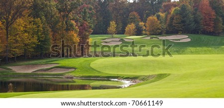 Panoramic view of a golf hole looking from the green back down the fairway to the tee. - stock photo