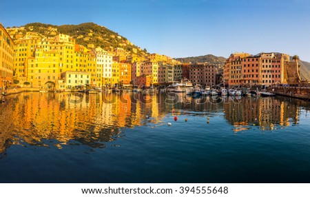 panoramic view of a harbor in a small resort town of Camogli in Italy with old colorful houses reflected in the sea