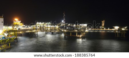 Panoramic view of a large offshore oil rig at night  - stock photo