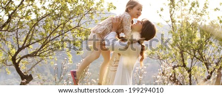 Panoramic view of a mother and her beautiful daughter playing together in a spring garden with flowers and sunshine, carrying the child and joyfully turning around, smiling. Family outdoors lifestyle. - stock photo
