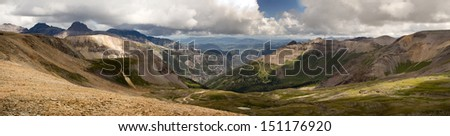Panoramic view of a Rocky Mountain pass in Colorado includes high altitude meadow, tree lined ridges, fields of weathered stones, crooked jeep trails, billowing clouds, and distant peaks and valleys. - stock photo