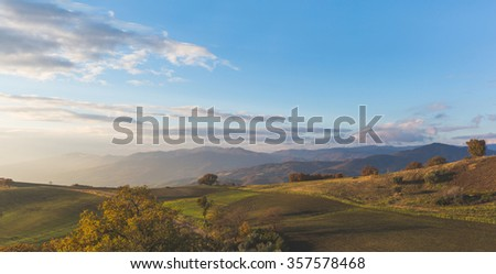 Panoramic view of a rural countryside in the southern Italy at dawn. There are hills and mountains with trees, forests and cultivated fields. Tranquil and serene location for a vacation. - stock photo