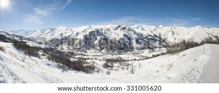 Panoramic view of a snow covered mountain range in the alps looking down valley - stock photo