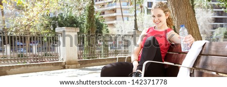 Panoramic view of a sporty and attractive young woman sitting down on a wooden bench in the city, taking a break from exercising and drinking mineral water during a sunny morning, smiling. - stock photo
