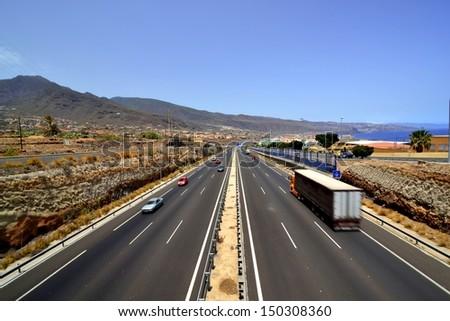 Panoramic view of a three-lane motorway near the sea coast - stock photo