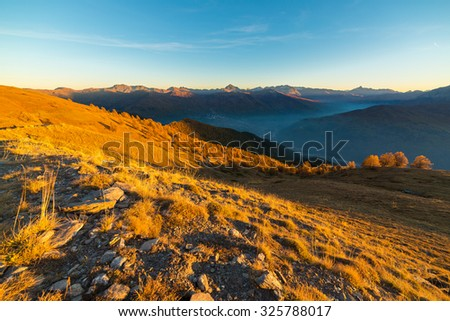 Panoramic view of alpine misty valley and mountain range in a colorful autumn with yellow meadows and high mountain peaks in the background. Wide angle shot at sunset.