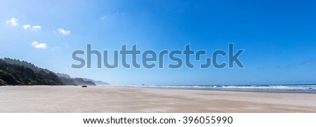 panoramic view of arcadia beach and castle rock on the west coast of the united states of america during a sunny day with the beach, people, sea, wave, cliff and forest - stock photo