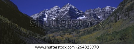 Panoramic view of autumn colors of Aspens reflecting in lake under Maroon Bells, Colorado, near Aspen - stock photo