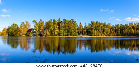 Panoramic view of autumn forest and houses reflection in pond, Aegviidu, Estonia