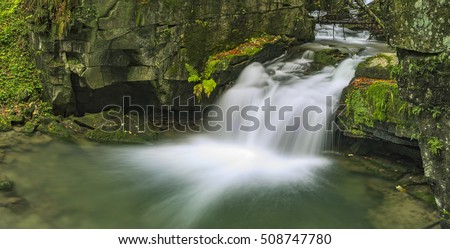 Panoramic view of autumn stream with waterfalls