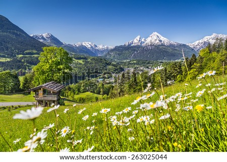Panoramic view of beautiful landscape with fresh green mountain pastures and snowcapped mountain summits in the Alps in springtime - stock photo