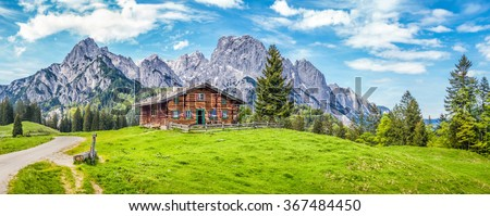 Panoramic view of beautiful mountain scenery in the Alps with traditional rural mountain chalet and fresh green meadows on a sunny day with blue sky and clouds in spring - stock photo