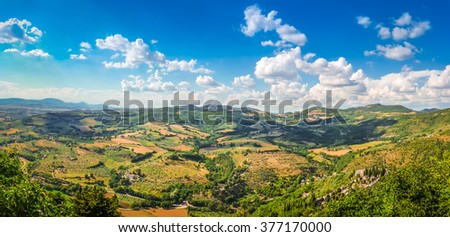 Panoramic view of beautiful Tuscany landscape with rolling hills, golden harvest fields, green wine gardens and an old cemetery from top of the ancient town of Assisi, Umbria, Italy - stock photo