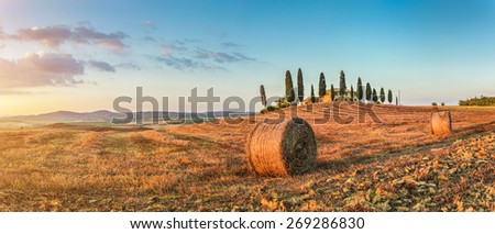 Panoramic view of beautiful Tuscany landscape with traditional farm house and hay bales in golden evening light at sunset, Val d'Orcia, Italy - stock photo