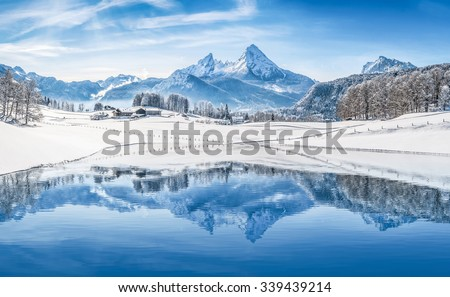 Panoramic view of beautiful white winter wonderland scenery in the Alps with snowy mountain summits reflecting in crystal clear mountain lake on a cold sunny day with blue sky and clouds - stock photo